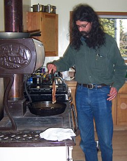 flipping bacon on cookstove